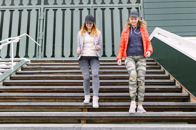 Lächelnder weiblicher rüttler, der auf treppenhaus läuft