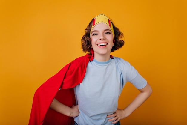 Lächelnder weiblicher superheld in der spielzeugkrone, die mit vergnügen aufwirft