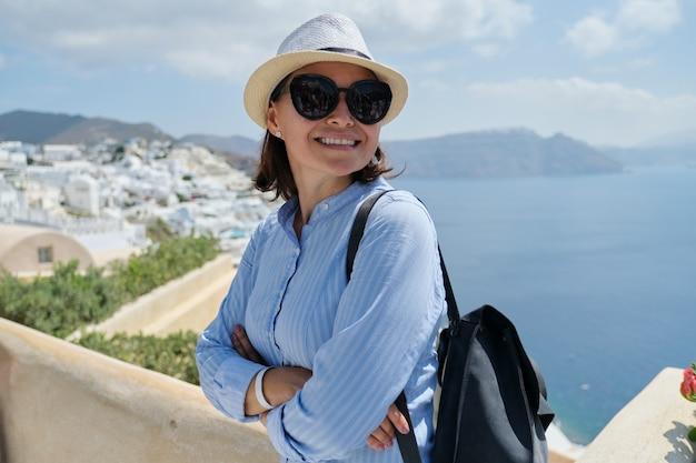 Lächelnder weiblicher tourist, der auf luxuskreuzfahrt im mittelmeer, griechenland, santorini reist