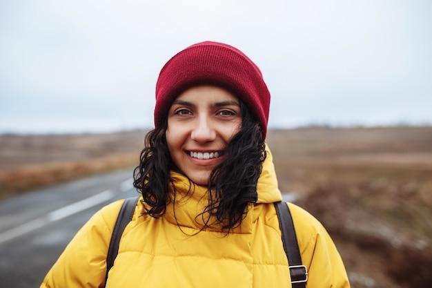 Lächelnder weiblicher tourist mit einem rucksack, der gelbe jacke und roten hut trägt, steht auf der straße.
