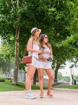 Lächelnder weiblicher tourist zwei, der im park hält karte und kamera steht