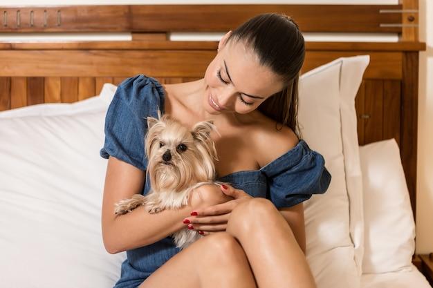 Lächelnder weiblicher umarmender hund auf bett
