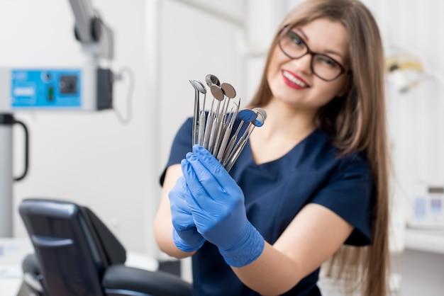 Lächelnder weiblicher zahnarzt mit den blauen handschuhen, die werkzeuge - zahnmedizinische spiegel und zahnmedizinische sonden im zahnmedizinischen büro halten