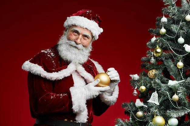 Lächelnder weihnachtsmann, der durch weihnachtsbaum steht