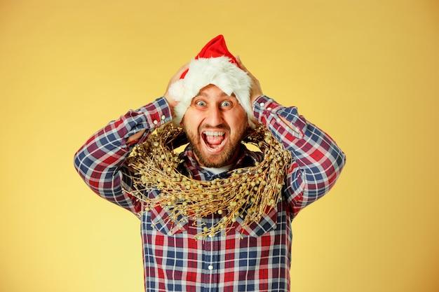 Lächelnder weihnachtsmann, der eine weihnachtsmütze auf dem orangefarbenen studio trägt