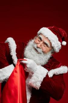 Lächelnder weihnachtsmann, der sack mit geschenken hält