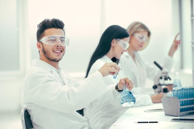 Lächelnder wissenschaftler, der im krankenhauslabor nach dem vorhandensein von coronavirus sucht. wissenschaft und gesundheit