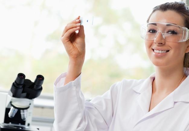 Lächelnder wissenschaftsstudent, der einen objektträger hält