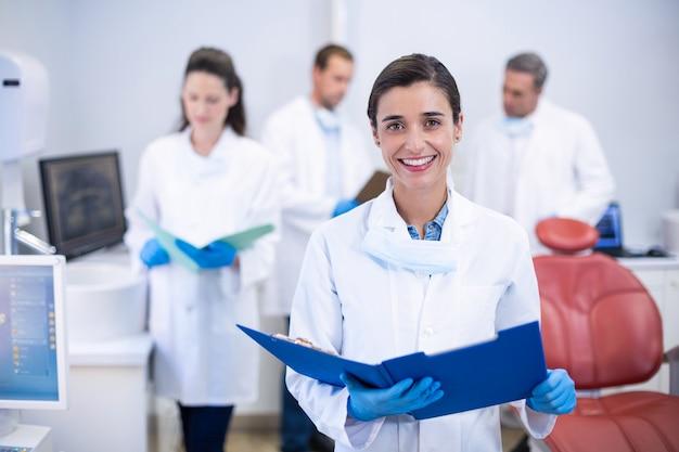 Lächelnder zahnarzt, der akte bei zahnklinik hält