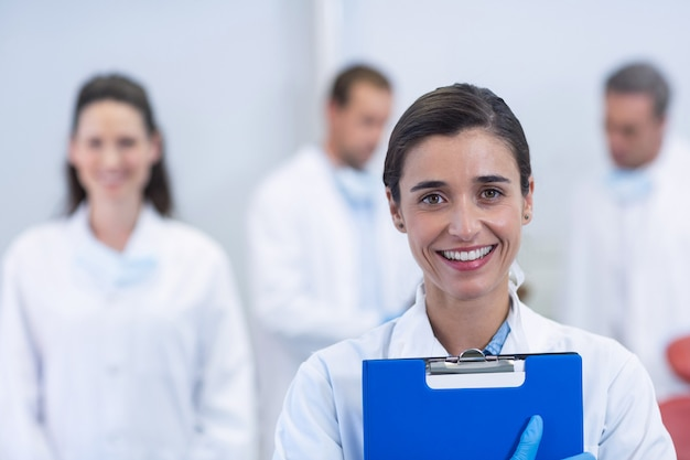 Lächelnder zahnarzt, der an der zahnklinik steht