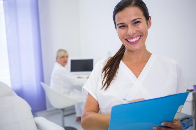 Lächelnder zahnarzt, der einen medizinischen bericht schreibt