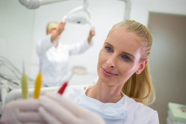 Lächelnder zahnarzt, der zahnärztliche werkzeuge betrachtet