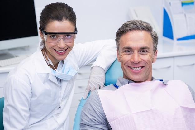 Lächelnder zahnarzt durch patienten in der medizinischen klinik