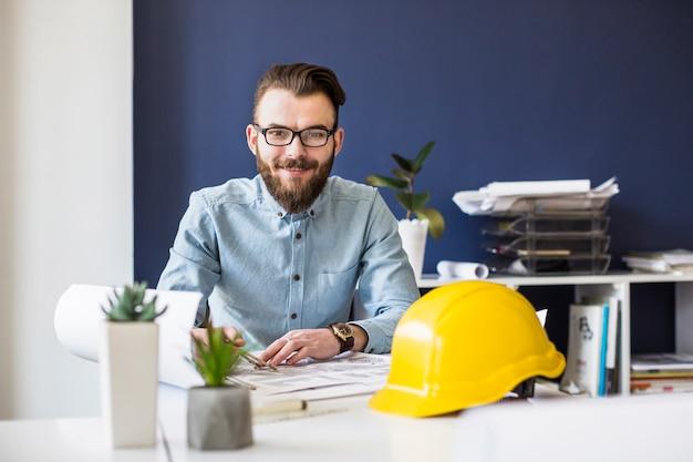 Lächelnder zivilingenieur, der an plan am arbeitsplatz arbeitet