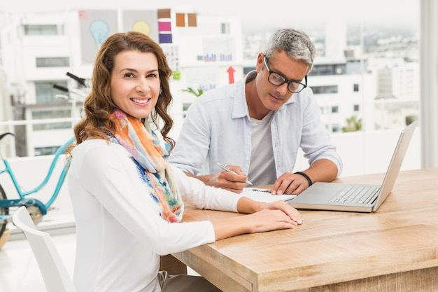 Lächelnder zufälliger designer vor ihrem arbeitskollegen