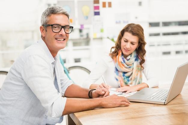 Lächelnder zufälliger designer vor seinem arbeitskollegen