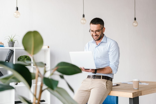 Lächelnder zufriedener mann der 30er jahre, der weißes hemd trägt, das auf tisch im büro sitzt und geschäftlichen chat auf silbernem laptop hat