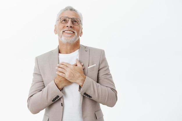 Lächelnder zufriedener und glücklicher älterer mann im anzug, der entzückt aufblickt