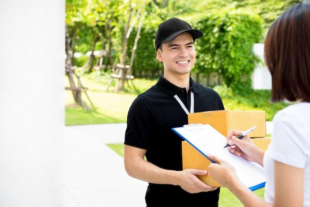 Lächelnder zusteller in schwarzer uniform, die paketboxen an eine frau liefert