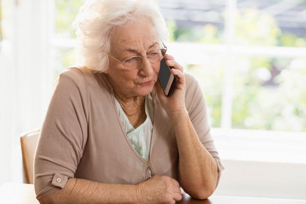 Lächelndes älteres frauentelefon, das zu hause nennt
