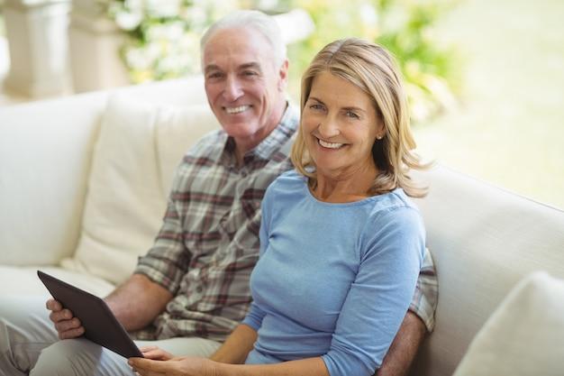 Lächelndes älteres paar, das auf sofa mit digitaler tablette im wohnzimmer sitzt