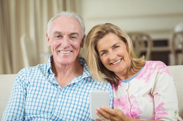 Lächelndes älteres paar, das auf sofa mit laptop im wohnzimmer sitzt