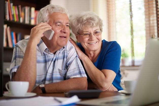 Lächelndes älteres paar, das geschäft per telefon macht