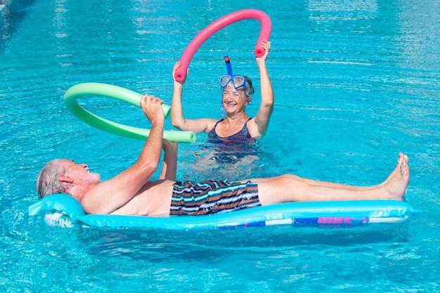 Lächelndes älteres paar, das übung im swimmingpool mit schwimmnudeln tut. glückliche rentner spielen im wasser des außenpools unter der sonne