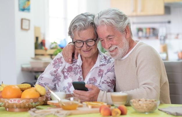 Lächelndes älteres paar, das während des frühstücks zu hause handy schaut