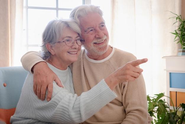 Lächelndes älteres paar, das zu hause umarmt sitzt. tragende brille der frau, die mit einem finger anzeigt. helles licht aus dem fenster