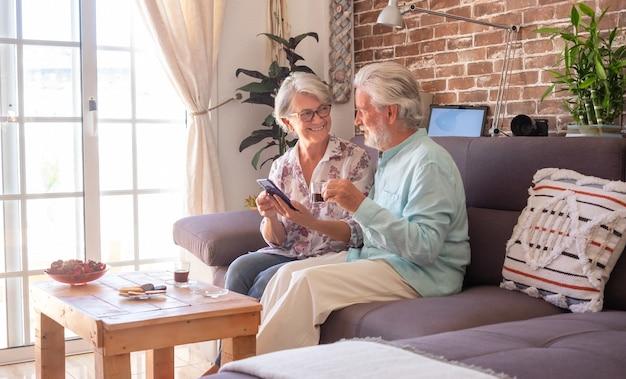 Lächelndes älteres paar zu hause, das auf sofa mit einem kaffee mit handy sitzt. backsteinmauer im hintergrund