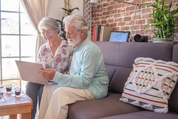Lächelndes älteres paar zu hause, das auf sofa mit laptop-computer sitzt. backsteinmauer im hintergrund