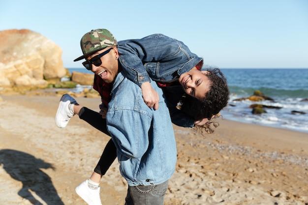 Lächelndes afrikanisches liebendes paar, das draußen am strand geht