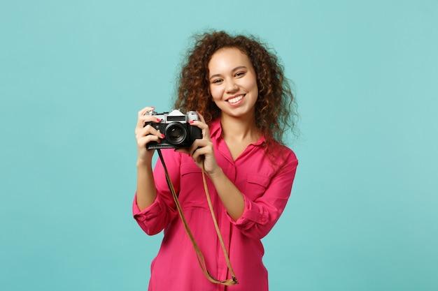 Lächelndes afrikanisches mädchen in freizeitkleidung, das ein foto auf einer retro-vintage-fotokamera macht, die auf blauem türkisfarbenem wandhintergrund im studio isoliert ist. menschen aufrichtige emotionen lifestyle-konzept. kopieren sie platz.