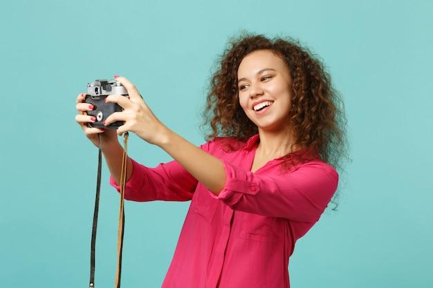 Lächelndes afrikanisches mädchen in freizeitkleidung, das selfie auf retro-vintage-fotokamera einzeln auf blauem türkisfarbenem hintergrund im studio macht. menschen aufrichtige emotionen lifestyle-konzept. kopieren sie platz.