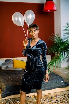Lächelndes afrikanisches mädchen mit luftballons in einem dunklen kleid, das im gemütlichen raum steht. geburtstag, neujahr, frauentagskonzept