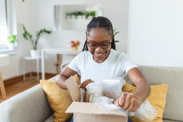 Lächelndes afroamerikanisches tausendjähriges mädchen sitzt auf dem sofa zu hause offenes karton-lieferpaket beim online-shopping, aufgeregte schwarze junge frau packt paket aus, das gut über das internet oder das web kauft