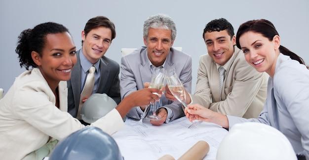 Lächelndes architectutal team, das einen erfolg mit champagner feiert