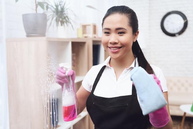Lächelndes asiatisches hausmädchen wäscht fenster mit stoff
