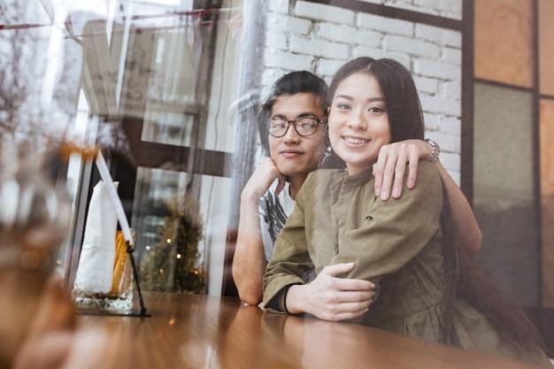Lächelndes asiatisches junges liebespaar im café