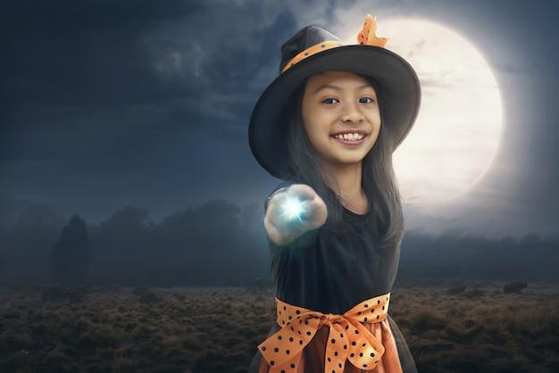 Lächelndes asiatisches kindermädchen, das ihre magische energie verwendet
