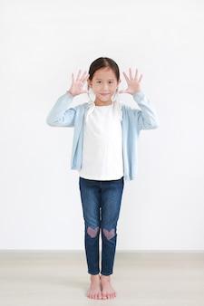 Lächelndes asiatisches kleines kind, das zehn stehende finger zeigt