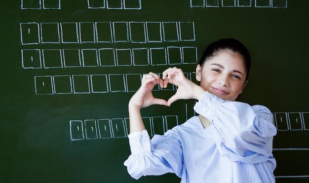 Lächelndes attraktives junges mädchen, das im klassenzimmer am college steht, das ein herz gestikulieren lässt, um ihre liebe der prüfung zu zeigen