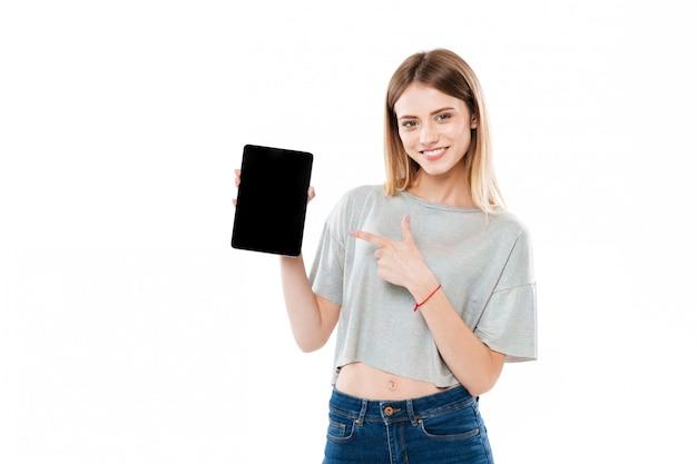 Lächelndes attraktives mädchen, das finger auf tablet-computer des schwarzen bildschirms zeigt