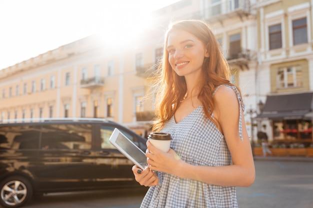 Lächelndes attraktives mädchen, das pc-tablette und tasse kaffee hält