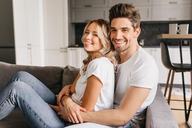 Lächelndes attraktives paar, das auf sofa sitzt und sich umarmt. zwei junge glückliche menschen teilen sich den morgen.
