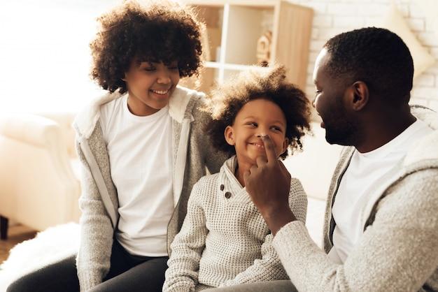 Lächelndes auf bett zu hause sitzen der glücklichen afroamerikanerfamilie