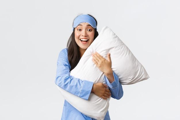 Lächelndes aufgeregtes hübsches asiatisches mädchen im blauen pyjama und in der schlafmaske, das weiches bequemes kissen umarmt und überrascht oder erstaunt auf kamera bei übernachtung, weißer hintergrund schaut.