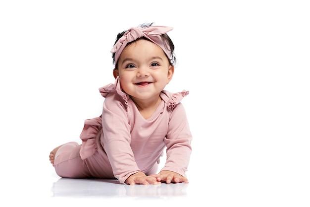 Lächelndes baby, das auf studioboden kriecht