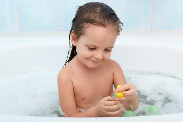 Lächelndes baby, das bad nimmt und mit spielzeug spielt.